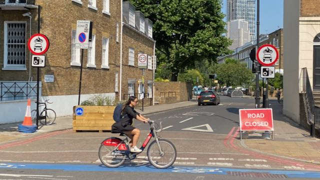 Woman cycles on CS7 A3 Clapham Road past a side road that's in the Oval-Stockwell LTN