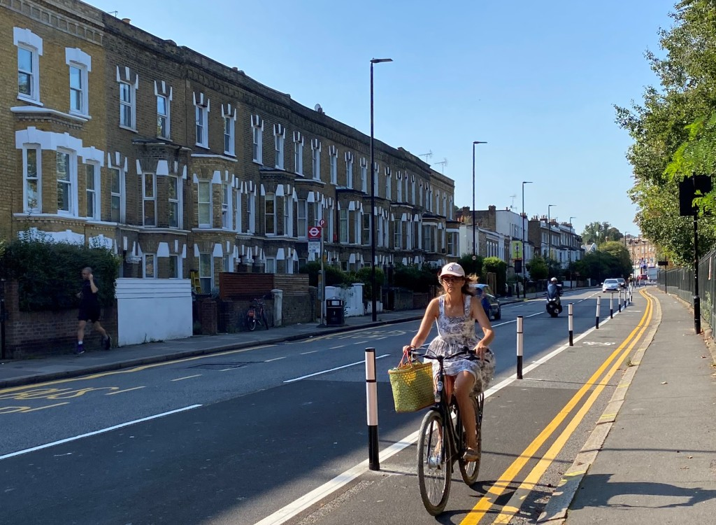Woman cycles on Norwood Road cycle way by Brockwell Park