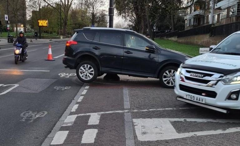 A driver's car on a bollard on the pavement of Brixton Hill at Dunbarton Rd